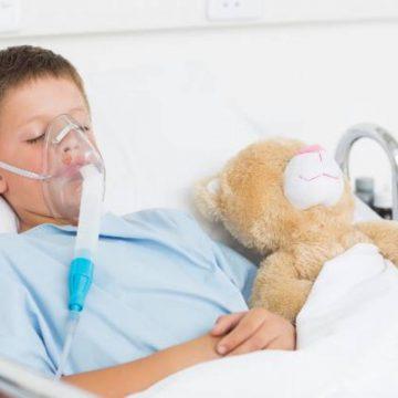 Sick boy wearing oxygen mask sleeping beside teddy bear in hospital bed
